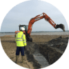 A maritime archaeologist with a digger carrying out a watching brief