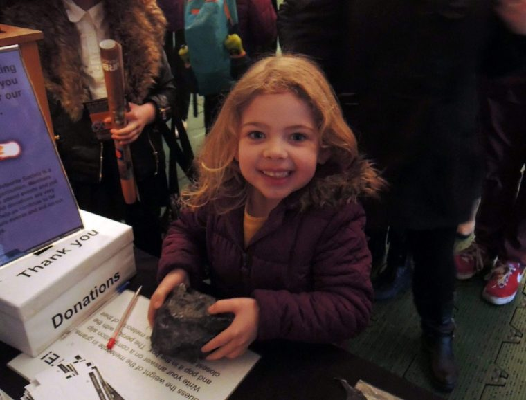 A beaming smile on a child's face whilst holding a real rock from space is the reason why collectors do outreach.