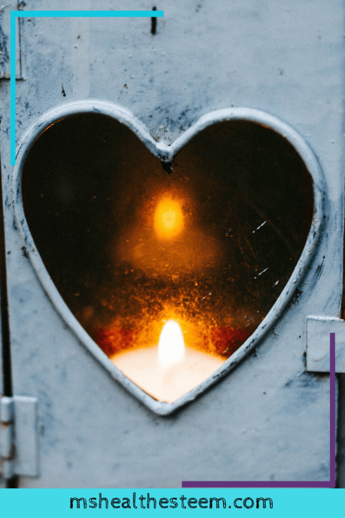 A heart shaped candle lantern with a lit candle inside as a metaphor for self-love burning within you