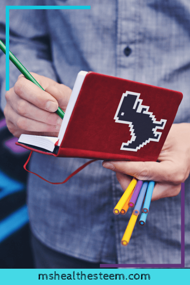 Man writing in red journal with a pixalated dinosaur on the cover