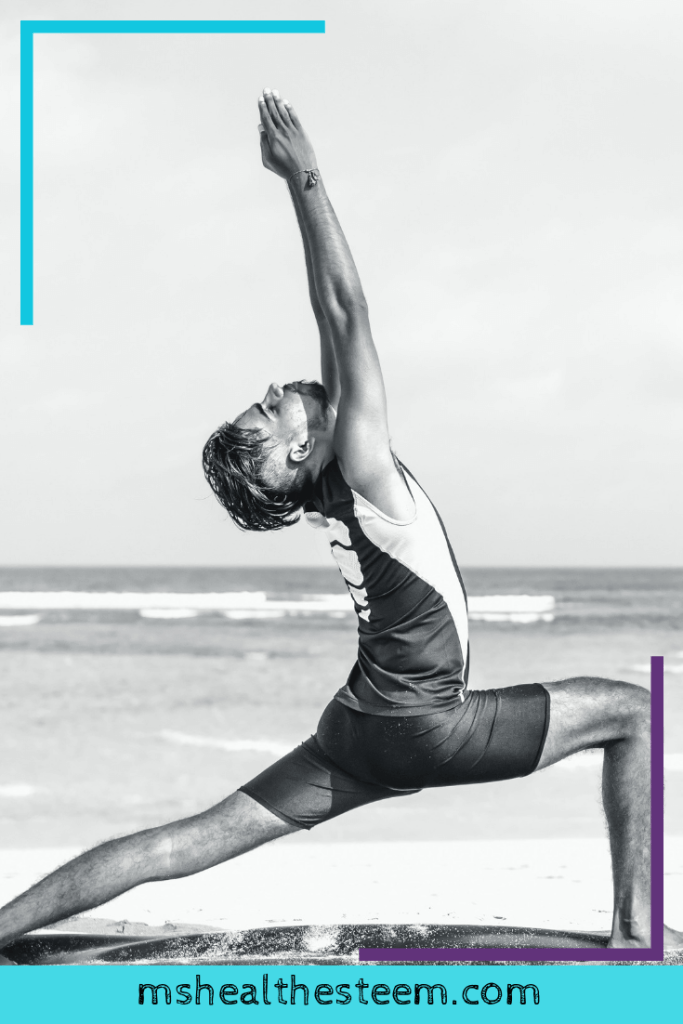 A black and white photo of a man enjoying yoga on the beach.