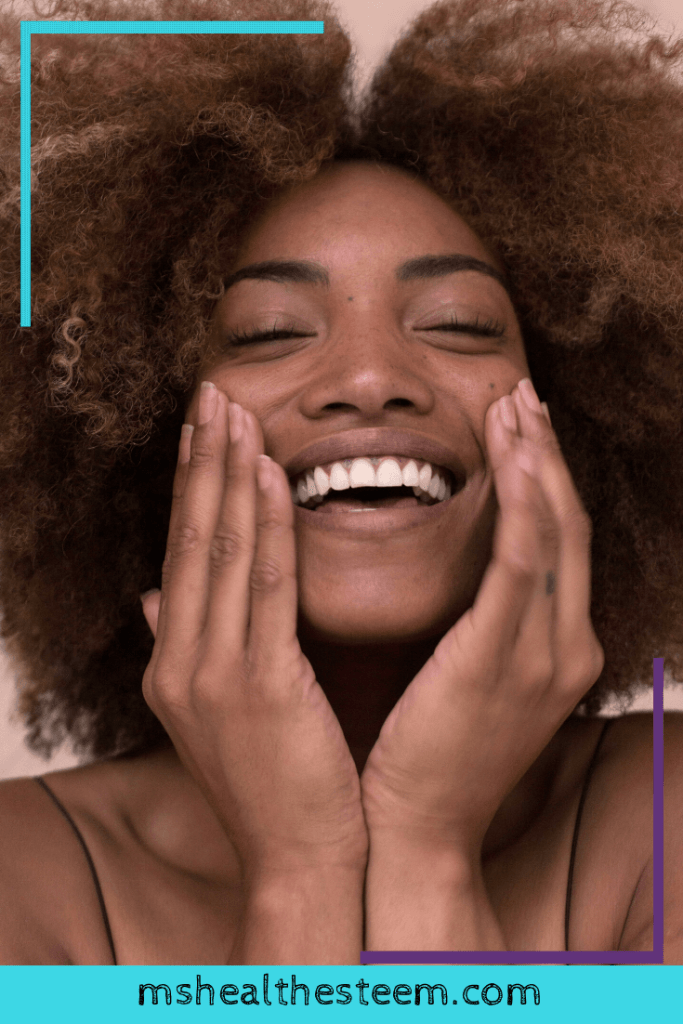 A woman smiles and touches her face as if applying moisturizer as part of her skin care routine