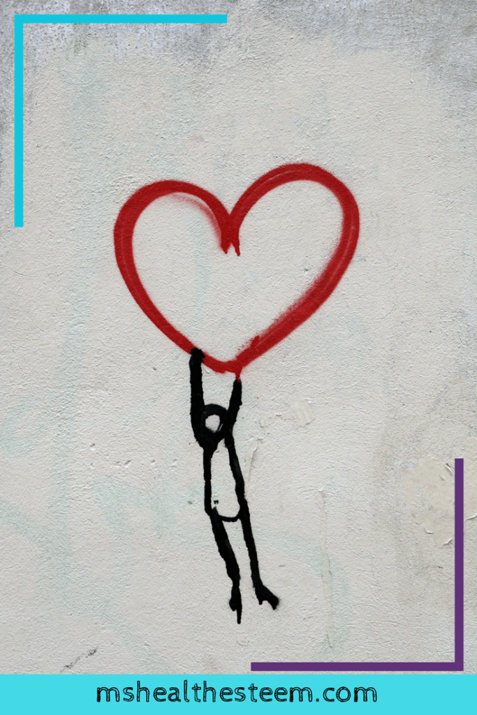 A spray painted heart with a little stick man holding onto it. Self-love helps to make positive thinking easier.