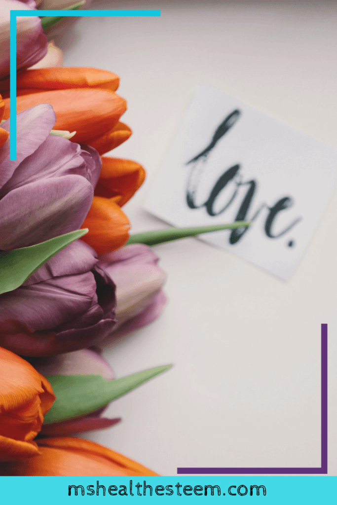 """A bouquet of orange and purple tulips lays on a white backdrop. Beside them sits a piece of paper with the word """"love."""""""