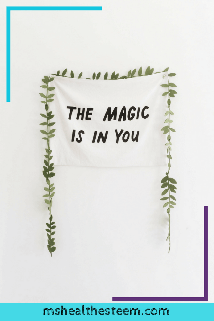 """A small flag that says """"The magic is in you"""" is decorated by a green, leafy plant."""