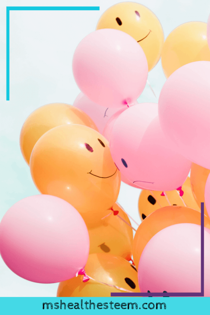 A group of pink and orange balloons. Some have smiling faces drawn on, while others have frowns.