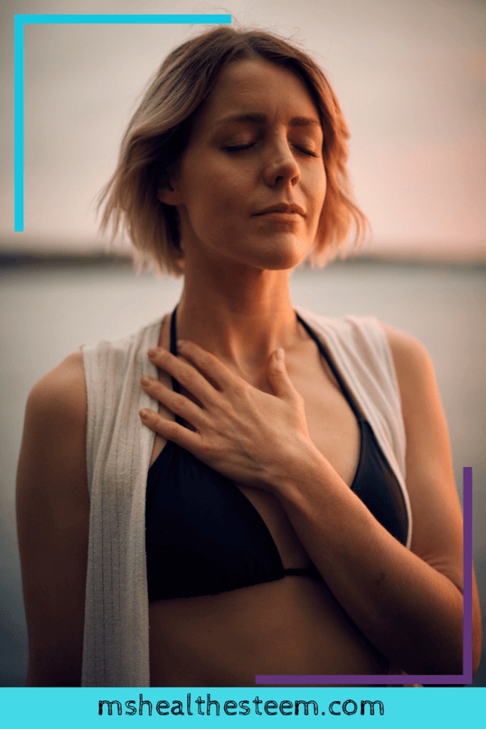A woman closes her eyes and touches her heart in a moment of mindfulness.