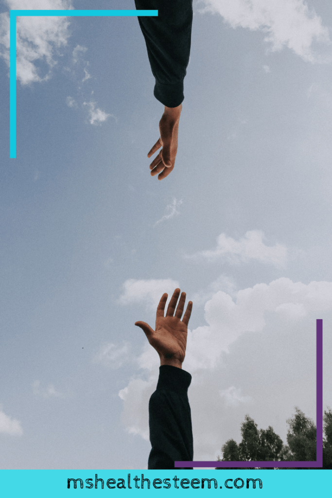 Two hands reach to each other for support. The sky can be seen in the background.