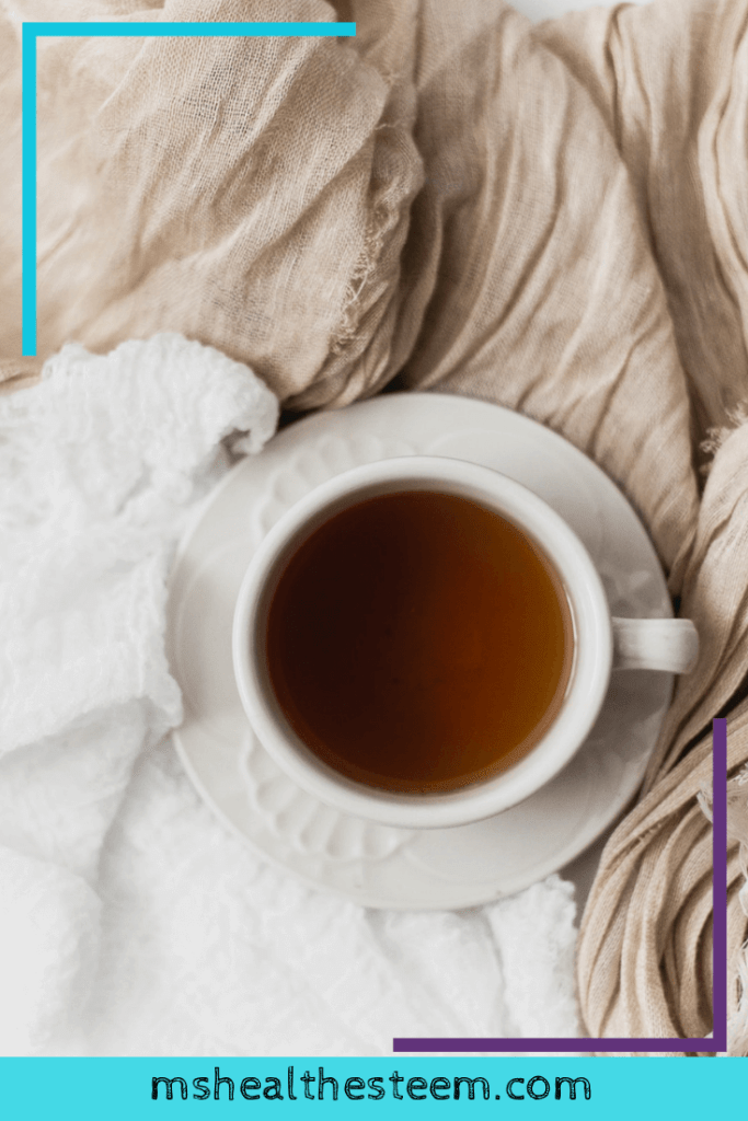 A cup of tea sits on top of cozy blankest. Relaxing and investing in downtime is a great way to work on reducing stress