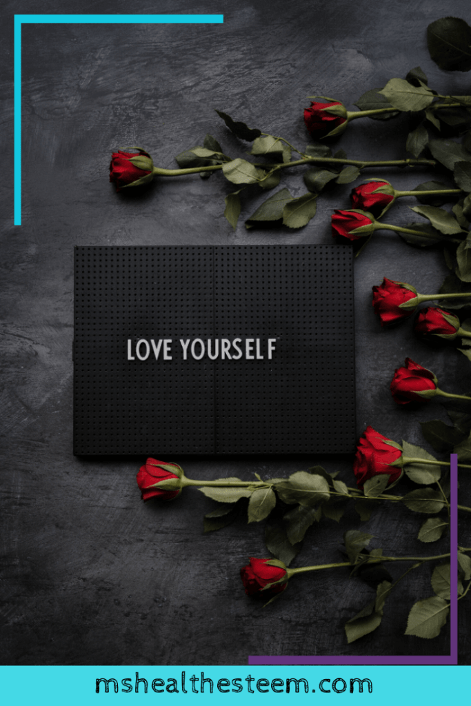 """A peg board says """"Love Yourself."""" Roses decorate the background."""