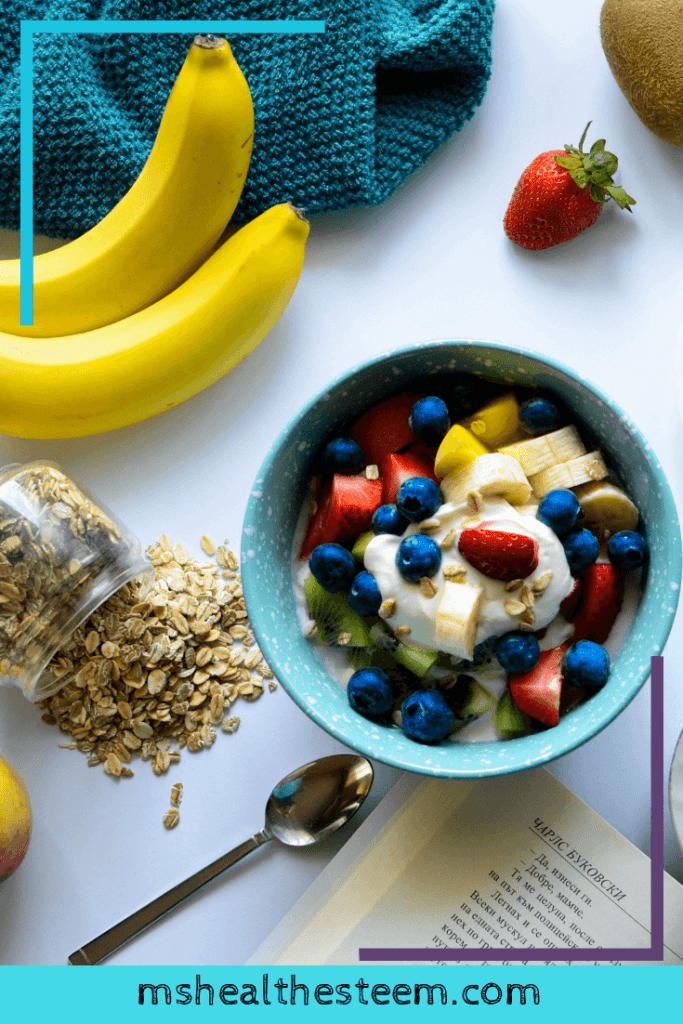 a bowl of fruit, yogurt and grain sits on a table beside bananas, oasts and a single strawberry. Breakfast is an important part of any healthy morning routine.