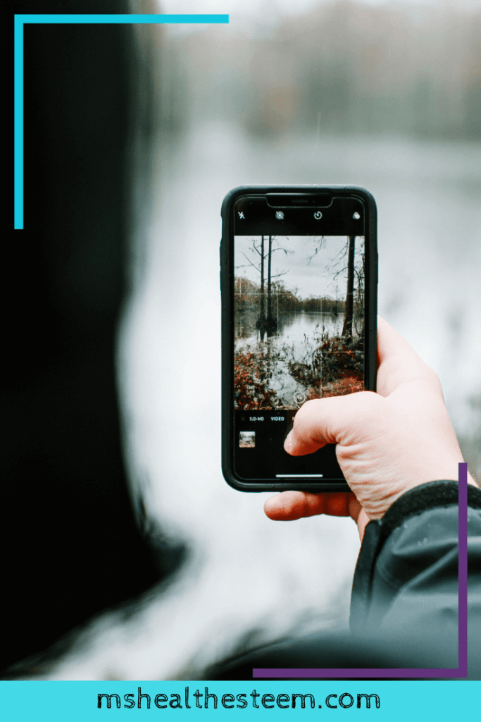 Someone holds up a phone to take a photo. The background is blurred but you can see a nature scene on the phone screen.