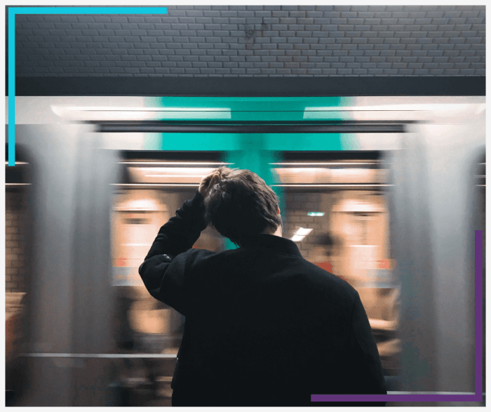 A man stands with his hand on his head watching a subway go by.