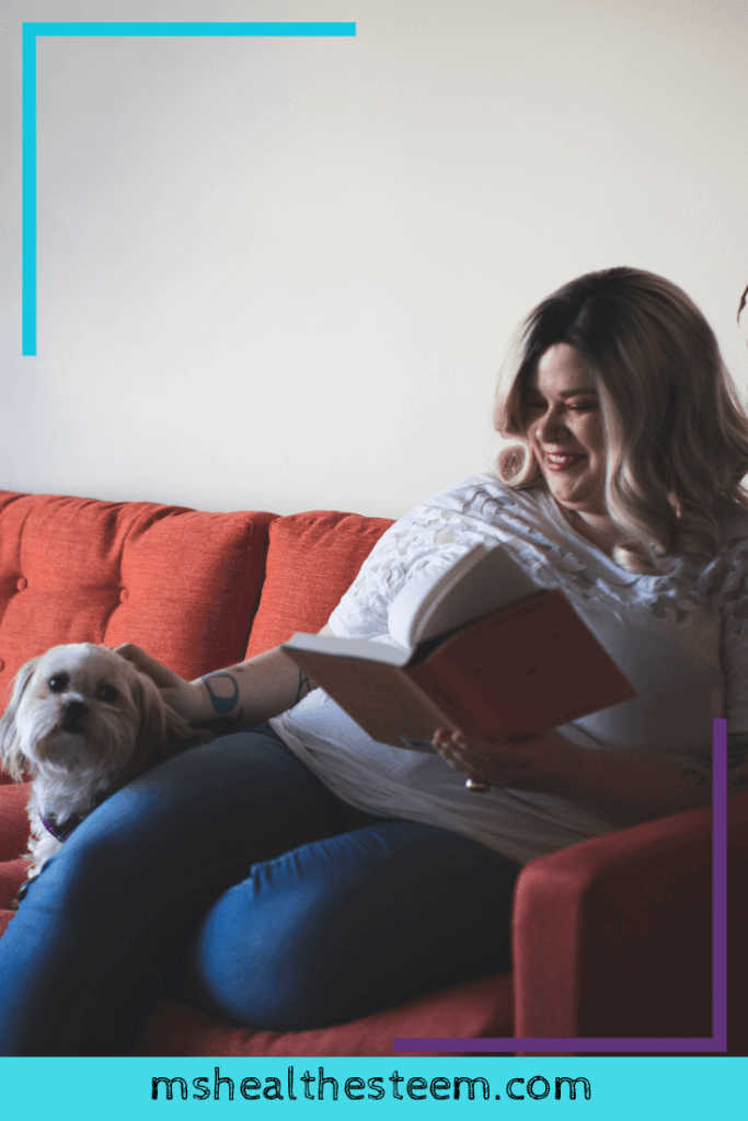 A woman sits on her couch with her dog, reading a book. A great way to relax during your self-care Sunday.