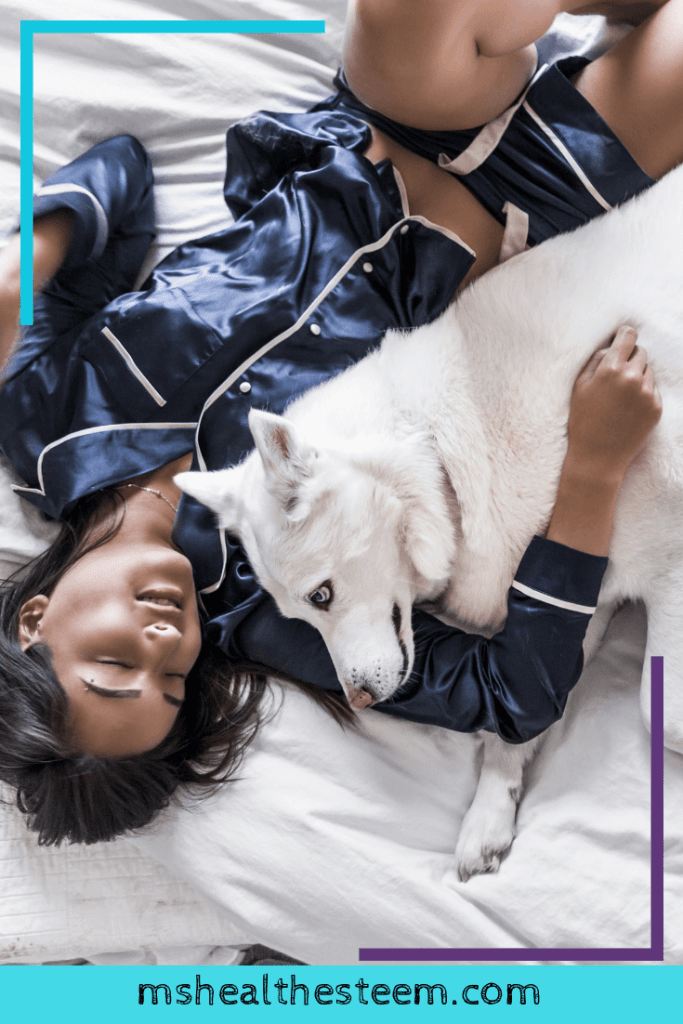 A woman cuddles her dog in bed. Cuddling with pets can be a great form of self-care.