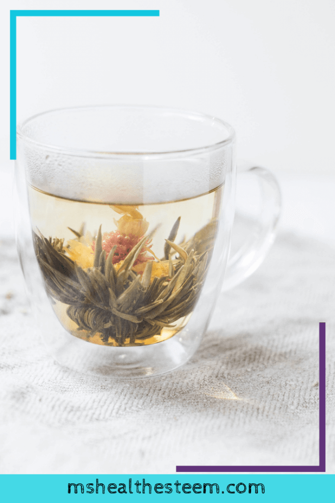 A clear glass mug with herbs and hot water. Tea can be a huge help to a sensitive stomach.
