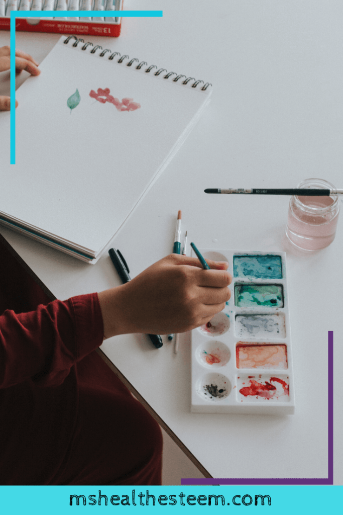 Someone paints in a journal, taking a moment to be creative and connect with themselves.