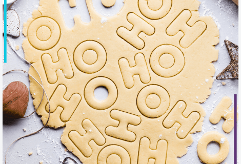 Sugar cookie dough sits on a table partially cut by H and O cookie cutters so it says HOHOHO