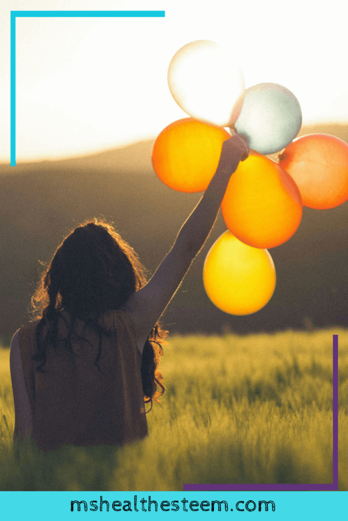 A woman holds a handfull of balloons up, as if in triumph