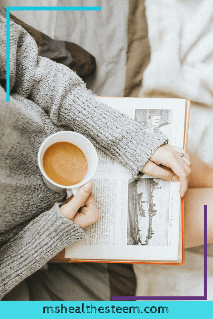 Someone sits down with a book and a cup of coffee. Prioritizing self-care and relaxing moments is an important part of being self-partnered.
