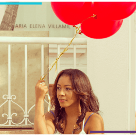 A woman sits outside holding onto red balloons