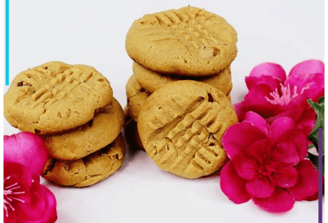 Two stacks of Peanut Butter Cookies sit on a white surface, decorated with pink flowers