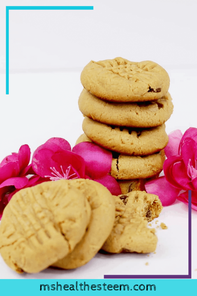 A pile of Peanut Butter Cookies sits on a white table, decorated with pink flowers.