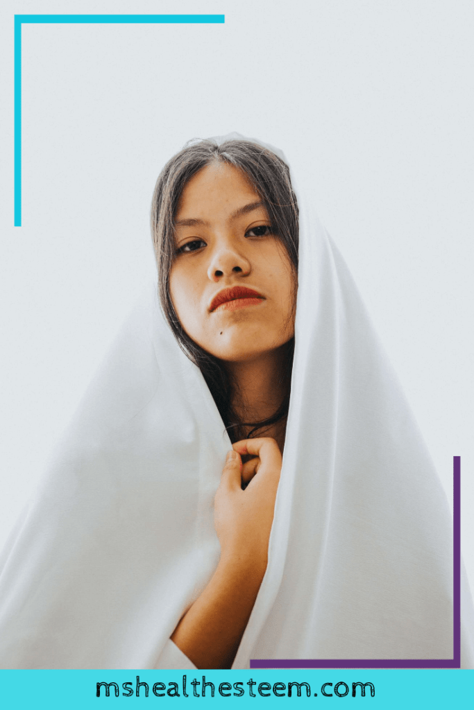 A woman sits with a white blanket draped over her head and overing her body. She gently holds the blanket with her right hand. And looks at the camera. She has a tough, frustrated expression - perhaps she's frustrated with BMI and it's obsessioin with predicting your ideal body weight.
