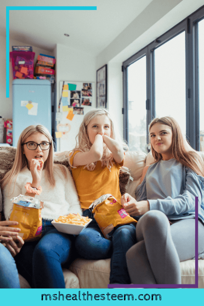 A group of young ladies on the sofa watching comfort shows with snacks