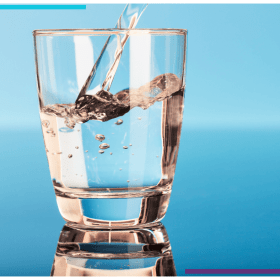 Drinking water being poured into a glass in front of a blue backdrop