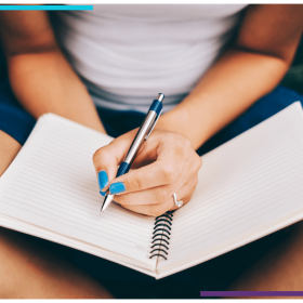 a woman sits cross legged and gets ready to write on the blank page in her gratitude journal