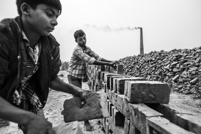 "Rasel (right) and Mohamed work at ""Nice"" brick factory. Their work entails shifting and carting sand from one place to another, as well as stacking bricks. On a good day they can earn up to 130 Taka a day. They are forced to work to help support their families. Although the law prohibits child labour, the practice is consistent throughout the region. Enforcement of existing laws is inadequate. Child labour is technically illegal but extremely widespread. Driven by poverty, it is often parents who are forced to push their children into work at an early age. (please note all the real names of the children is this story have been changed to protect their identity)"