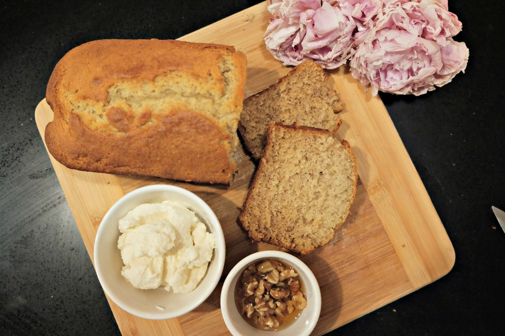 Banana bread loaf sliced on a chopping board.  A bowl of creme fraiche cheese and another of honey infused walnuts next to it.