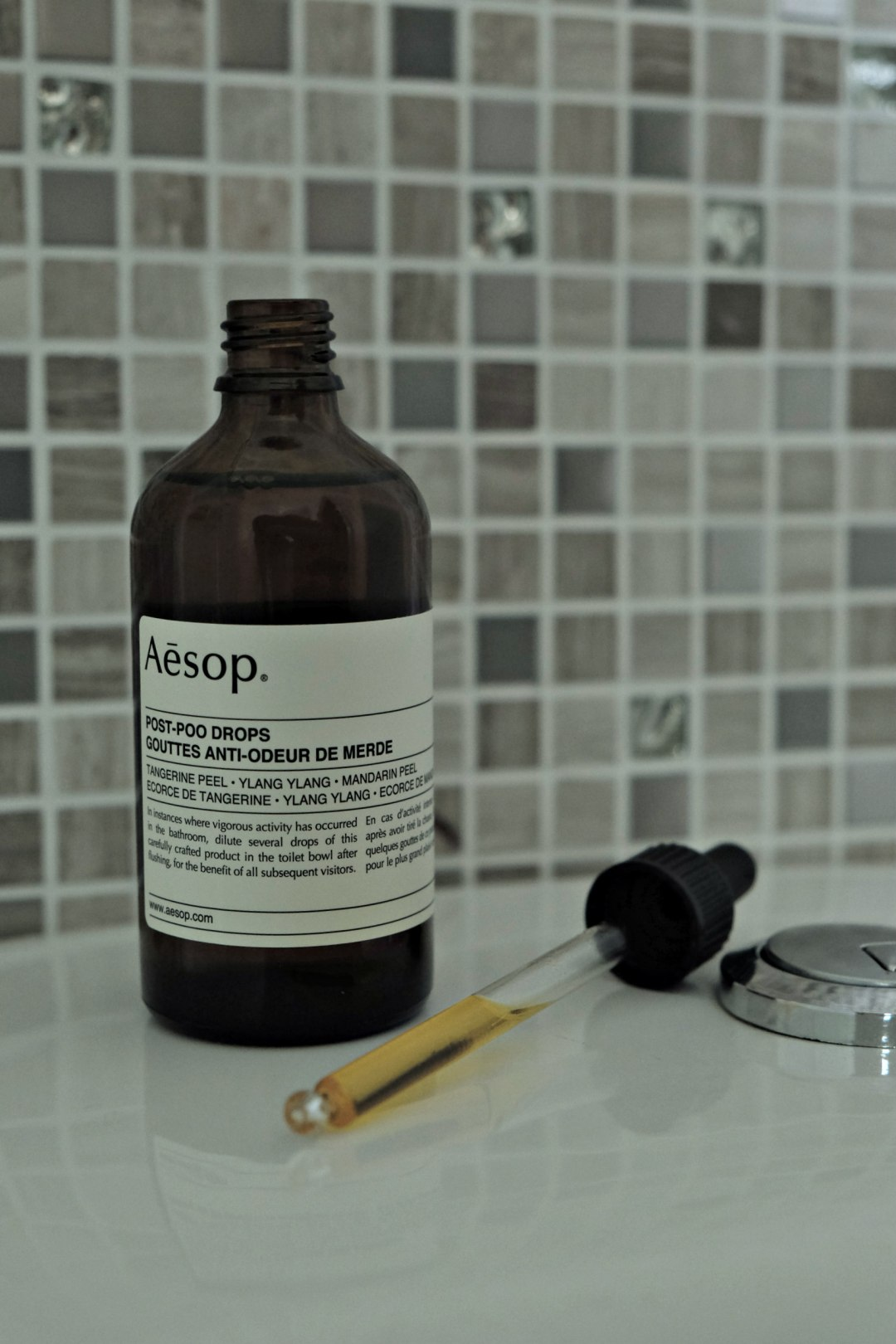 Picture of bottle of Aesop post poo drops open with dropper next to it.  You can see the liquid in the dropper.