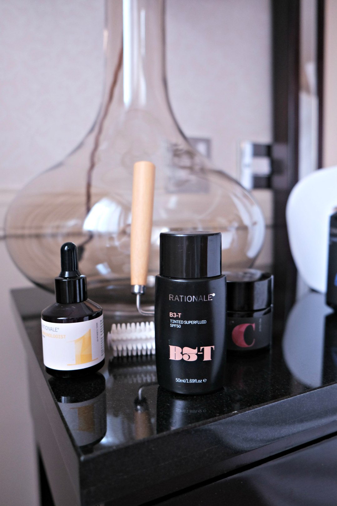 Close up picture of my skincare products, face roller and mask on a side table in a lovely hotel.