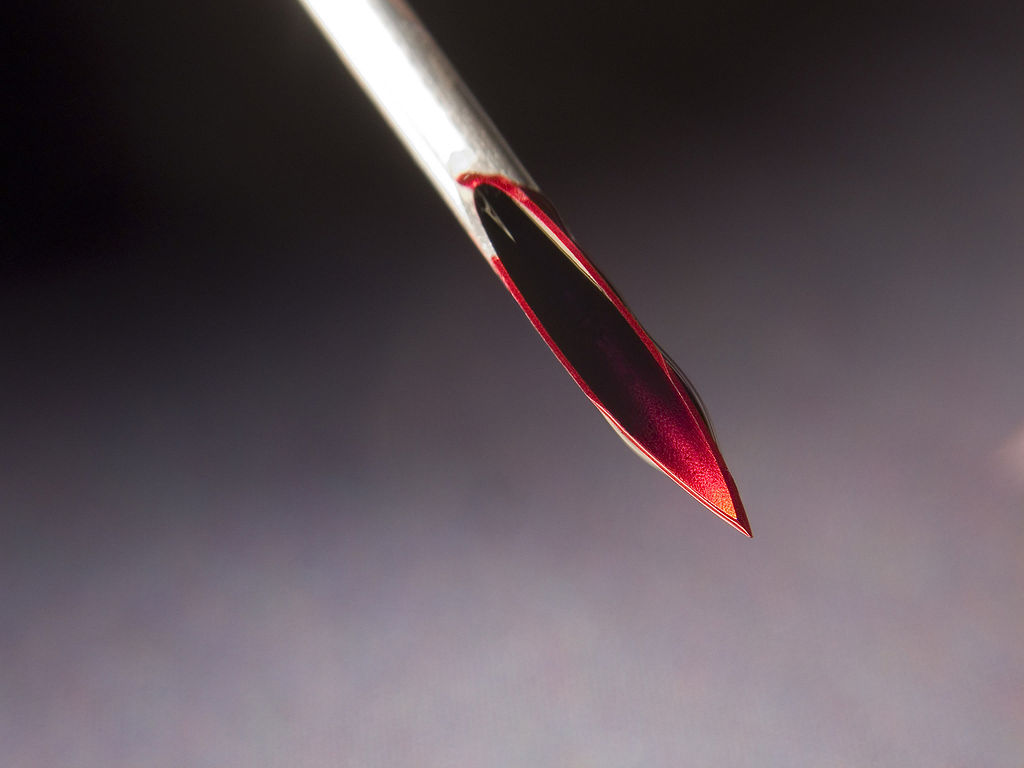 toronto play piercing workshop needle play 101 - Image description: a close up shot of a hollow needle with blood all over the tip, set against a background that fades from black to grey