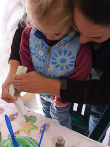 A mom helping a little girl decorate a star shaped sugar cookie with green frosting.