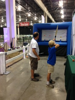 A boy uses a bow and capped arrow to shoot into a blow-up target.