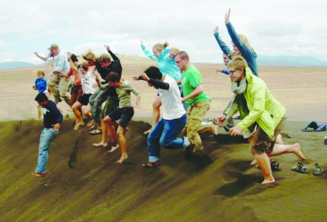 """A past group of MSUM students jump off a sand dune at a place known as """"Shifting Sands"""" found in a valley between mountains in north Tanzania. The sand dunes move many inches per year."""