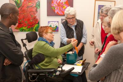 """Opening of the """"Flowers, Flores, Ubaxa"""" exhibition at the Mount Baker Neighborhood Center for the Arts. Juliet Byrne Gossett demonstrates how she adapted instruments to allow her to paint despite having limited use of her hands."""