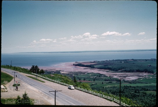 Large wide landscape shot from the lookoff near Minas Basin in Nova Scotia. Taken in 1961. Shows road at bottom of the frame with a white car parked to the side of the road next to steep hill. Body of water in the distance. Mid afternoon, sunny day.