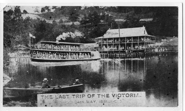 A black and white photograph showing an artistic depiction of the passenger boat, the Victoria leaving Springbank Park on its last voyage which ended in the tragic drowning of the majority of people on board. In the left foreground two people sit in a rowboat looking towards the Victoria which is steaming away from the dock on the opposite shore. Many people are standing on the two tiered pavillion and on the bank watching. To the left of the Victoria, in the background can be seen part of another passenger boat. (Cairncross Collection, Ivey Family London Room, London Public Library)