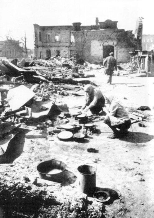 Жители Сталинграда готовят пищу у развалин своего дома, разрушенного немецкими бомбардировками.
