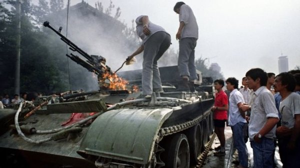 Протестующие осматривают уничтоженный танк