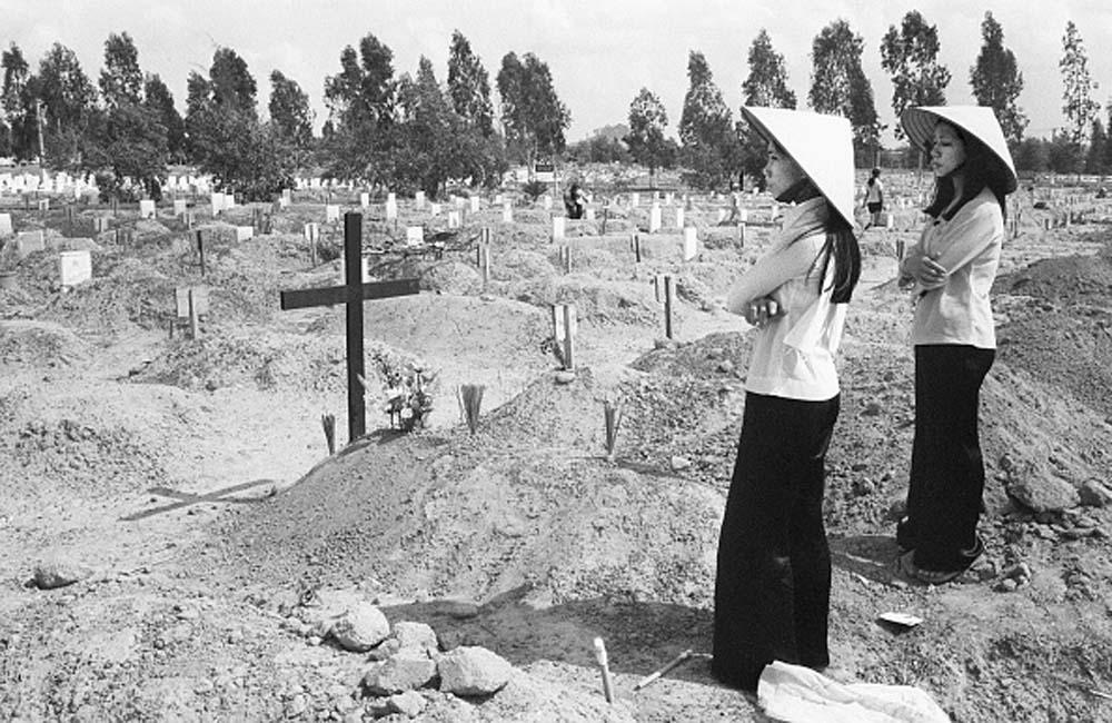 Две вьетнамские женщины оплакивают своих родственников на военном кладбище Бьенхоа, поскольку США начали эвакуировать свое посольство в Сайгоне. 29 апреля 1975