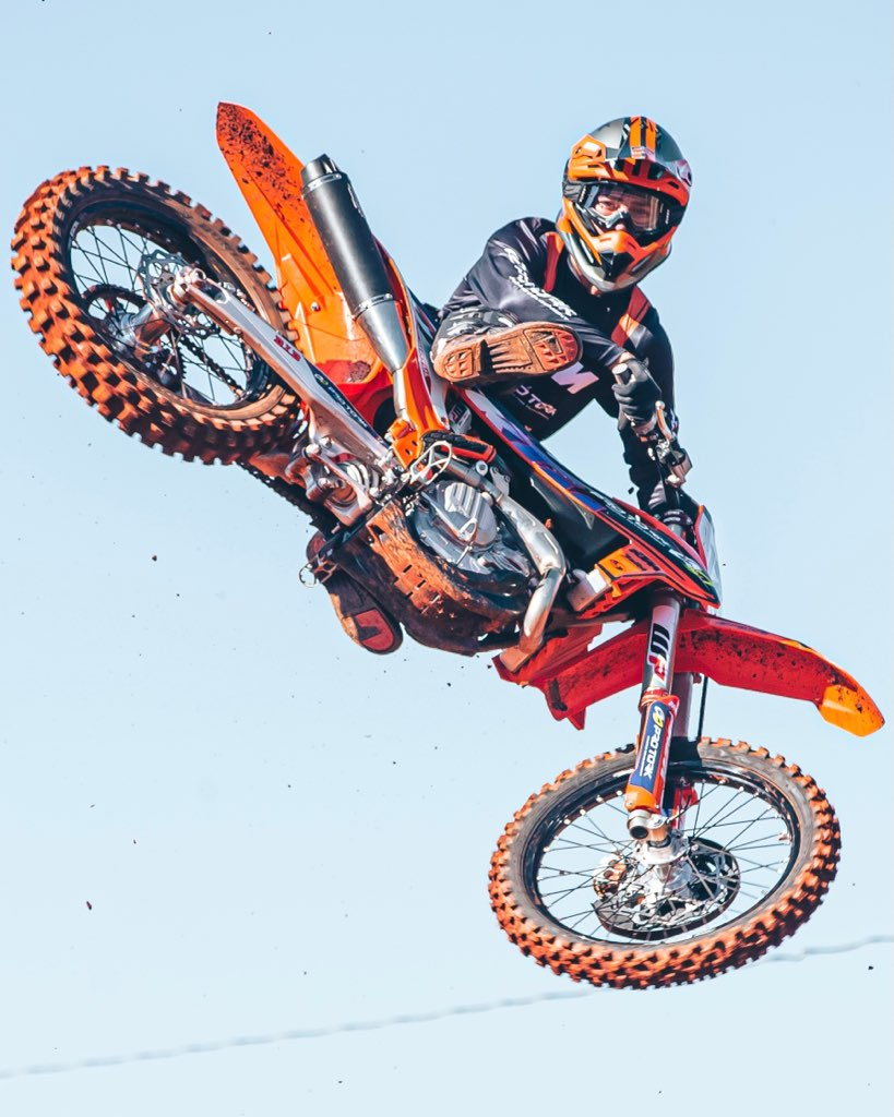 Anthony Rodríguezlooks to the camera while he whips his dirt bike over a jump at the motocross track.