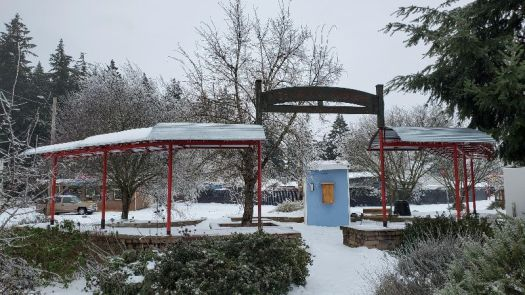 Picture of the Arleta Triangle Project and Community Care Cabinet covered with snow in SE Portland, Oregon during a winter event in February, 2021.