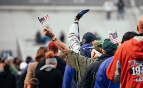 A veteran waves an American flag high towards the fans as he, and many others, take the field at Floyd Stadium, November 7 2015. The veterans were honored at half time at MTSU's football game Saturday night.