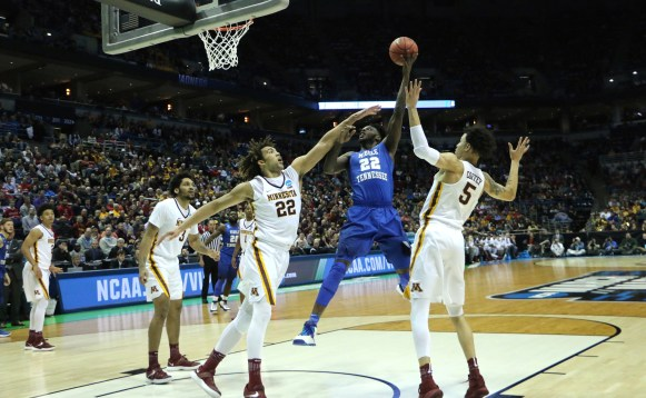 MTSU forward JaCorey Williams (Blue) puts up a shot over Reggie Lynch (White) in an NCAA Tournament first-round game against Minnesota in Milwaukee, WI on March 16, 2017. (MTSU Sidelines/Tyler Lamb)