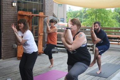 Sarah Kurtz teaching a skill from behind at Mayday Brewery's yoga session on Saturday, May 25, 2017. (Wesley McIntyre / Sidelines)